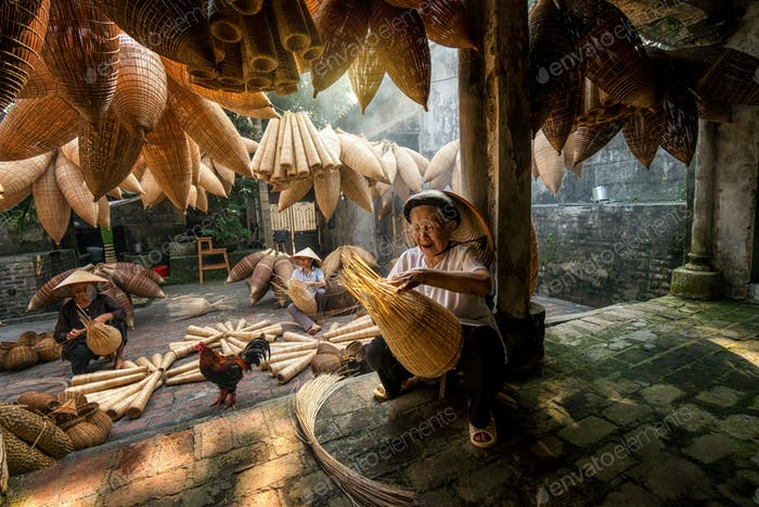 Old Vietnamese female craftsman making the traditional bamboo fish trap or weave at the old house