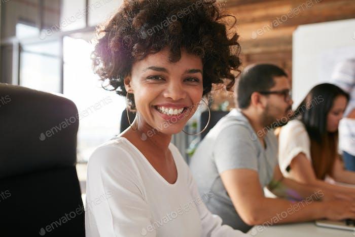 Fröhliche afrikanische Frau im Konferenzraum mit Kollegen