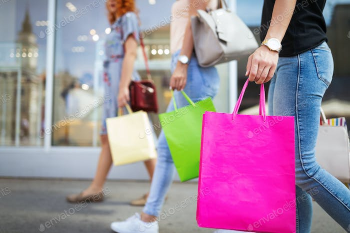 Sale and travel, happy people concept. Women with shopping bags in the ctiy