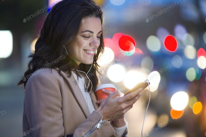 Pretty young woman using her mobile phone while holding cup of coffee in the street at night.