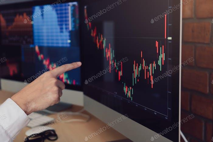 Primer plano de mano empresario apuntando gráfico y análisis bursátil en la computadora en la oficina.
