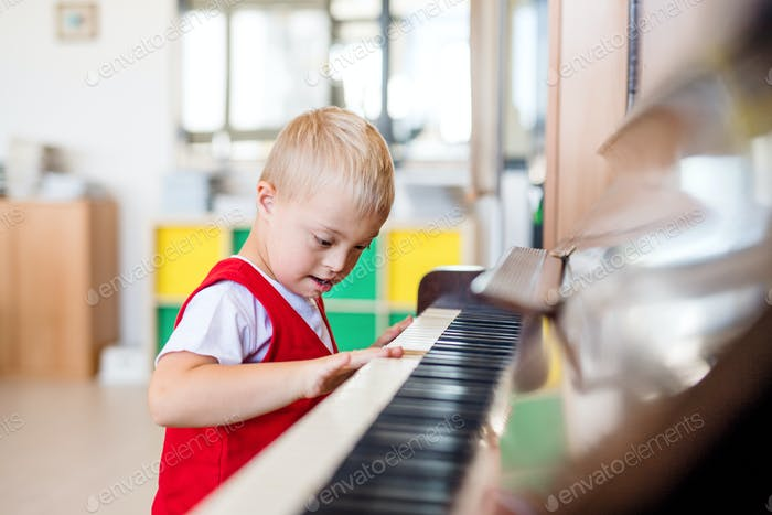 Ein Down-Syndrom Schuljunge sitzt in der Schule und spielt Klavier