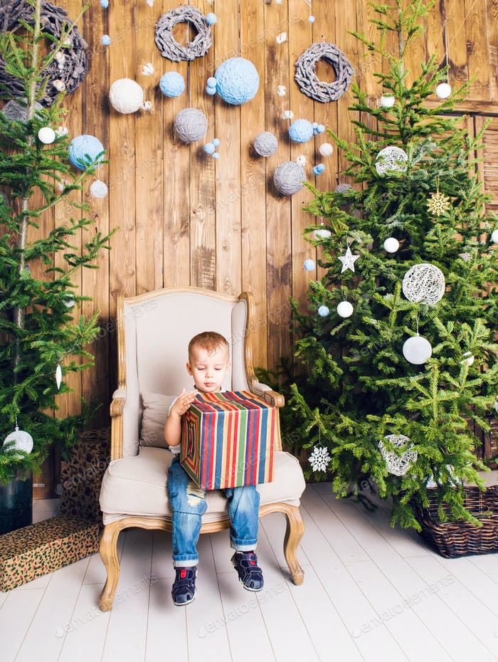 Boy with christmas gift near Christmas tree