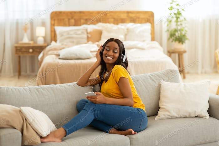Pretty black lady with smartphone and headset sitting on cozy sofa and listening to music at home