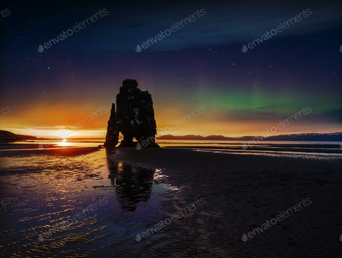 Sternenhimmel und Nordlichter in einem spektakulären Felsen im Meer an der Nordküste Islands
