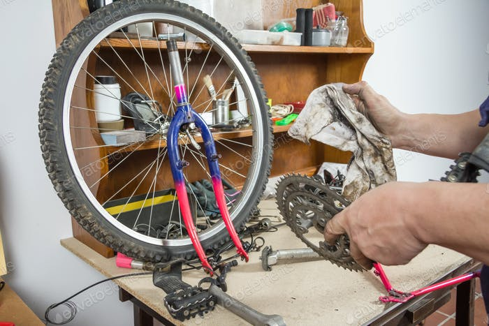 Hands of bicycle mechanic cleaning chainring bike