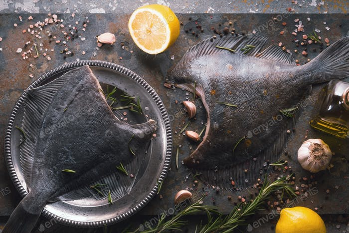 Raw flounders with different seasoning on the stone background