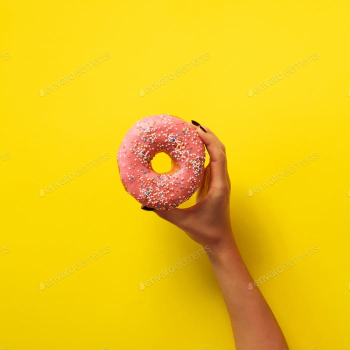 Woman hand holding delicious pink donut on yellow color background. Top view banner with copy space