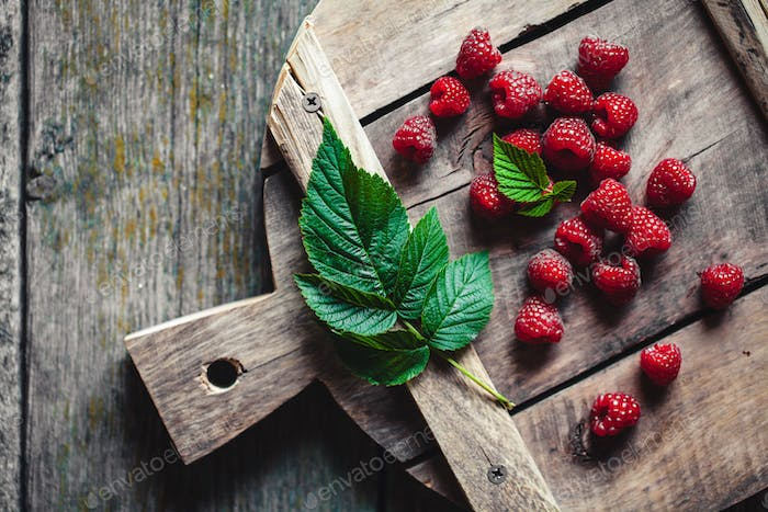 Ripe red raspberries on a wooden cutting board, Old accessories, vintage style