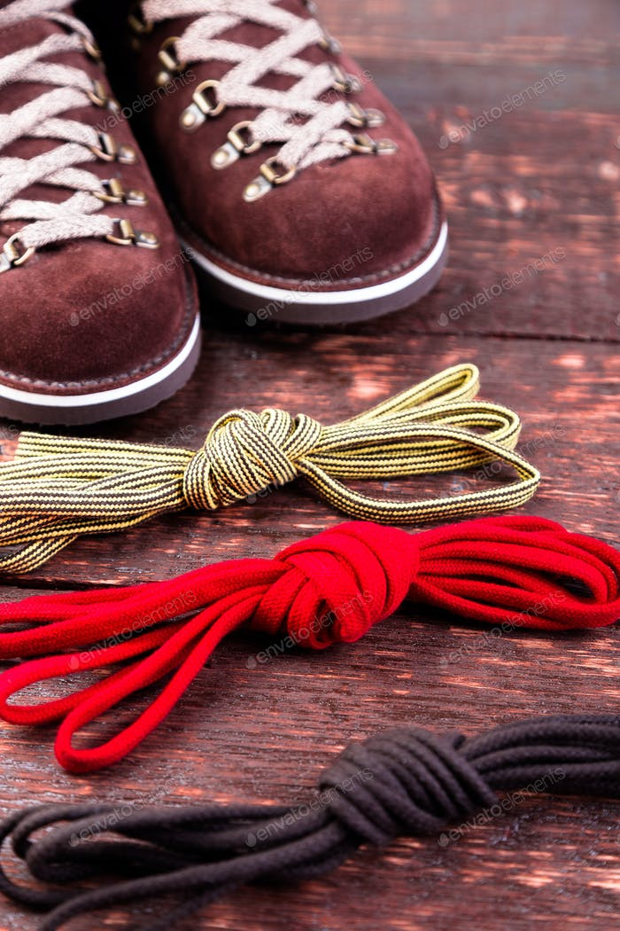 Brown man suede boots and shoelaces on wooden background. Autumn or winter shoes.