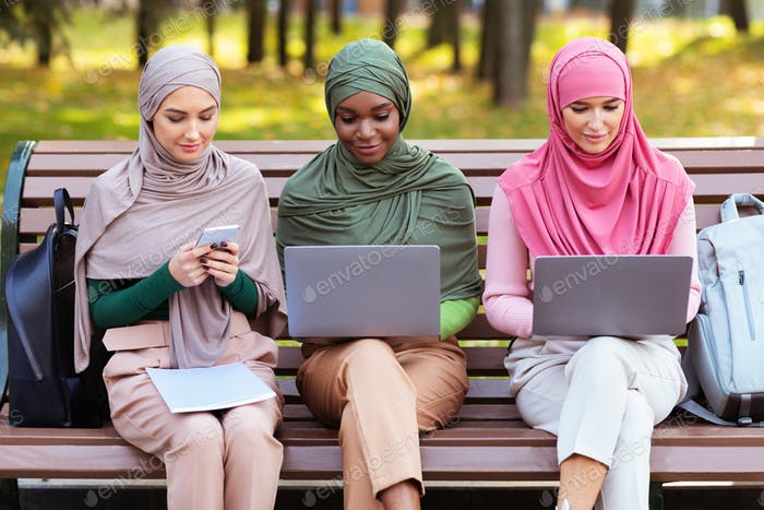 Arab Ladies Using Smartphone And Computers Learning Online In Park