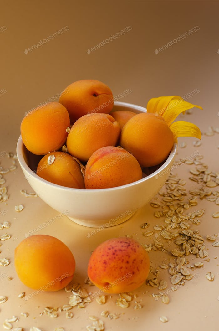 Fresh apricots on a white table strewn with oatmeal.