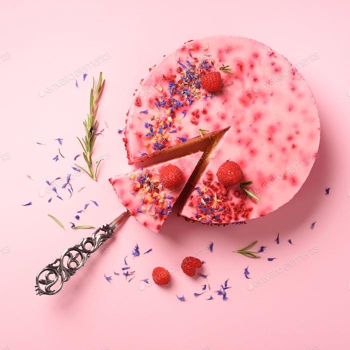 Köstlicher Himbeerkuchen mit frischen Beeren, Rosmarin und trockenen Blüten auf rosa Hintergrund. Kopierbereich