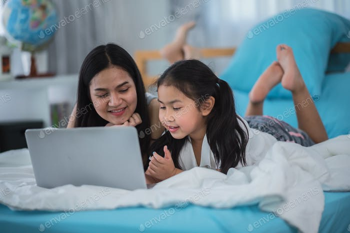 children and girl sisters having fun to watching online video on laptop computer cyberspace