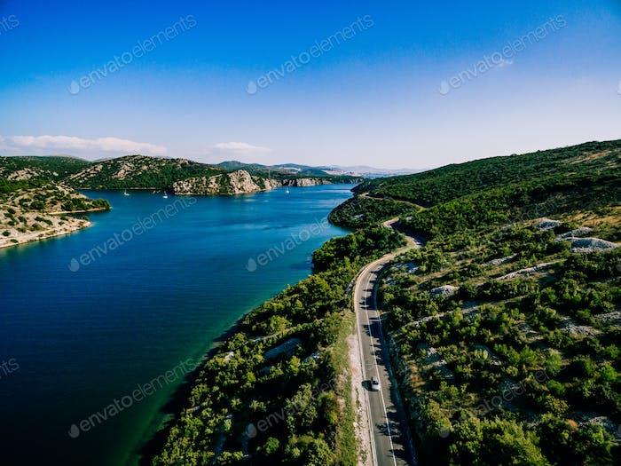 Luftaufnahme der Straße in der Nähe des blauen Meeres und grünen Berges im Sommer Kroatien.