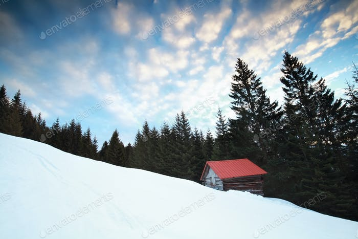 old wooden hut in snowy Alps