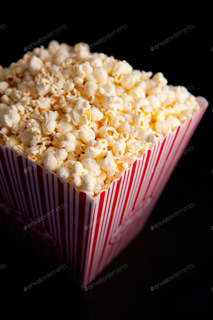 Close up of a box of pop corn against a black background