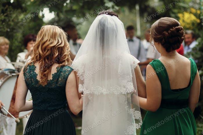 Beautiful brunette bride under veil in white wedding dress