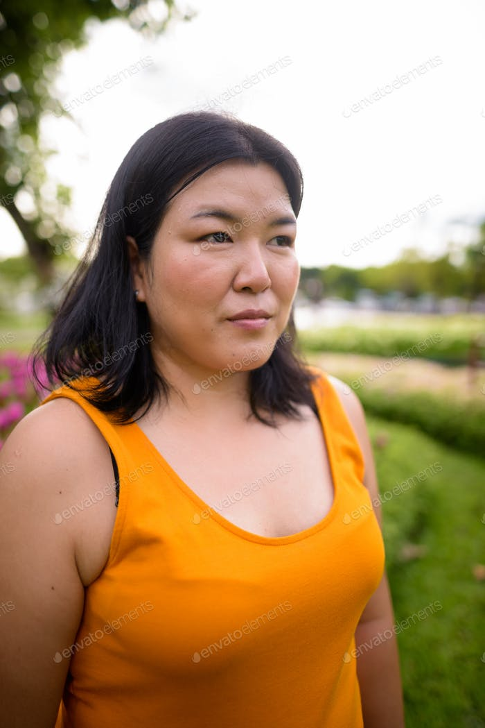 Beautiful overweight Asian woman thinking in park