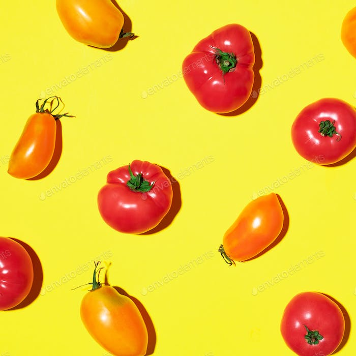 Yellow and red tomatoes pattern on yellow background. Flat lay, top view. Summer minimal concept