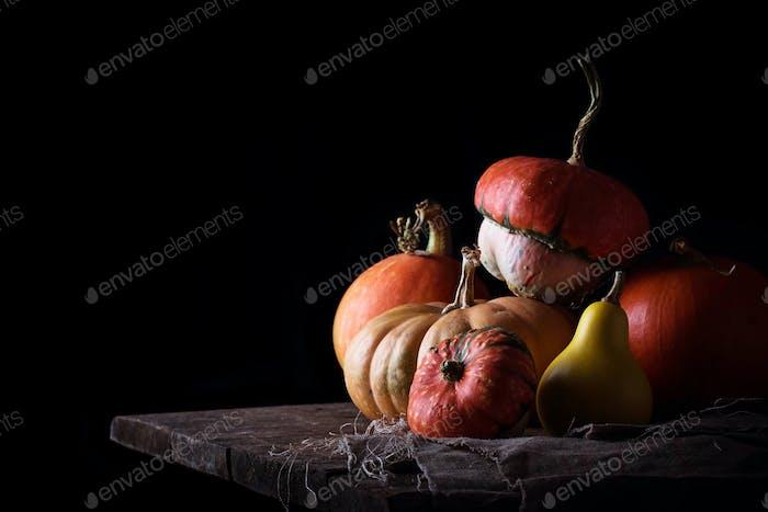 Pumpkins on wooden table in dark background