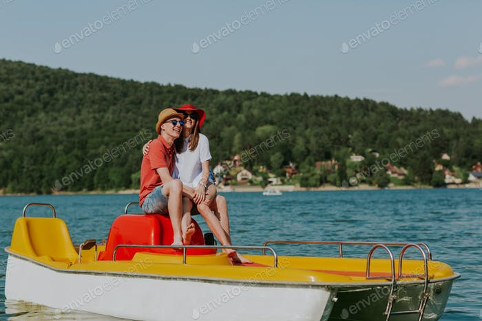 Shot of happy couple sitting on pedal boat.