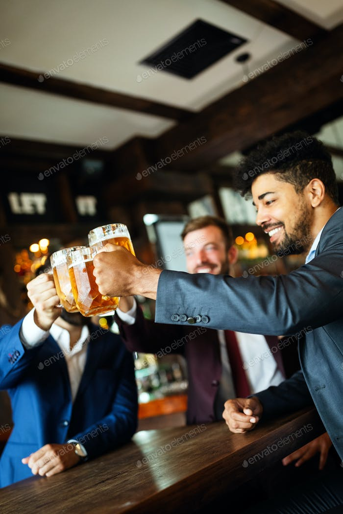 People, friendship and celebration concept. Happy business male friends drinking beer at pub