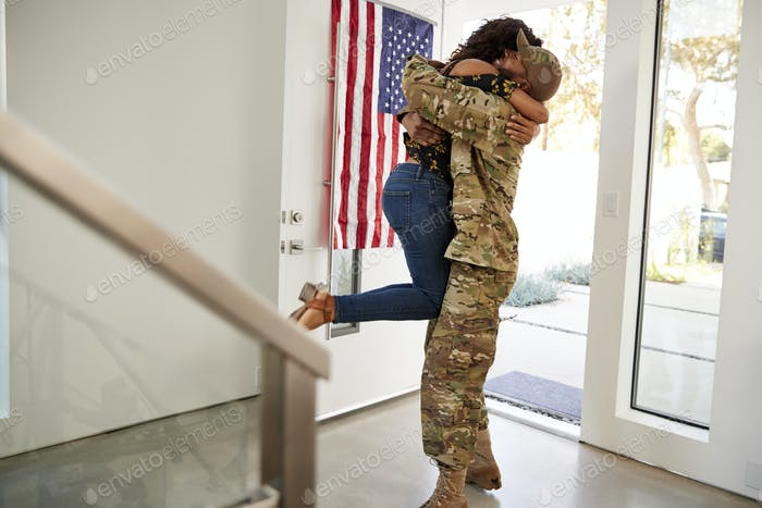 Returning millennial black soldier lifting his wife off her feet in their home, side view