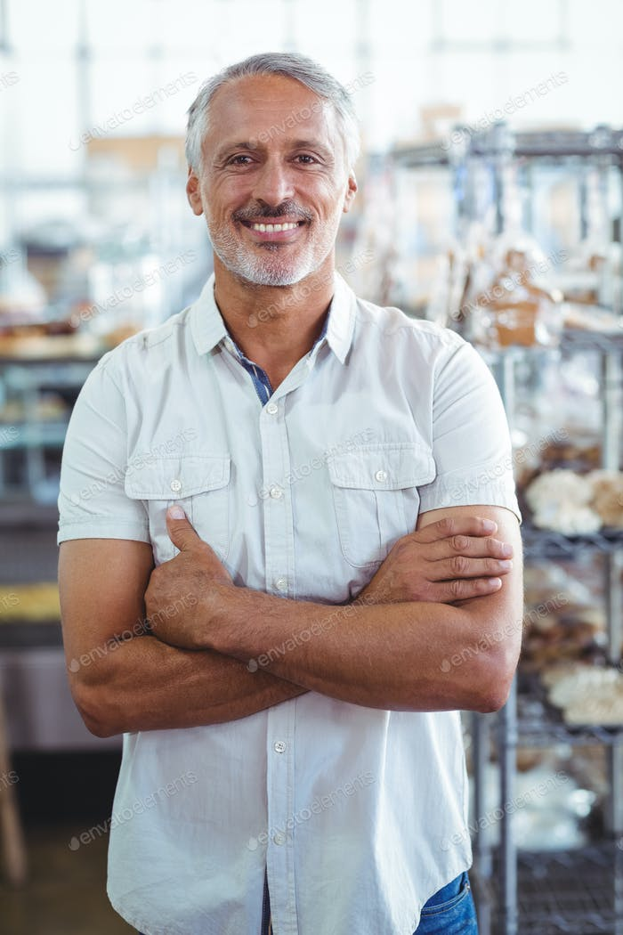 Smiling bakery owner standing with arms crossed at the bakery