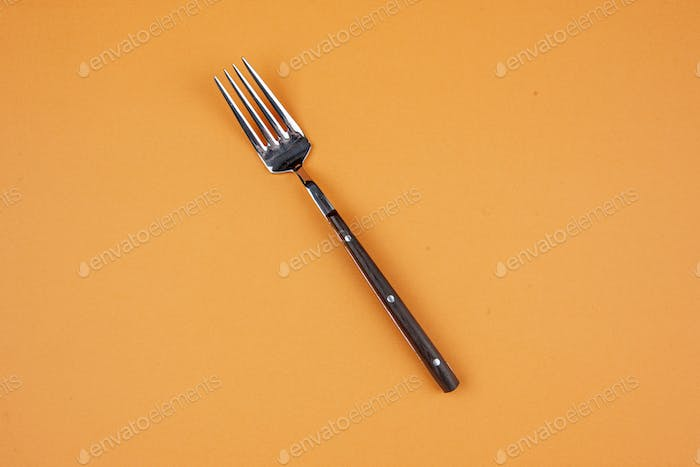 Overhead view of elegant metal fork in the middle on golden background with free space