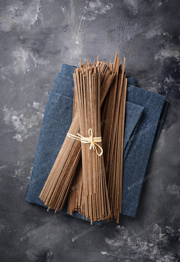 Raw uncooked Japanese soba noodles on grey bacground