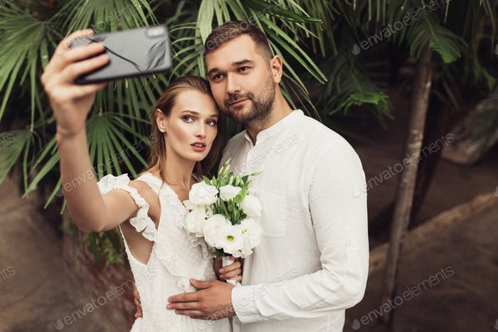 Young handsome groom in shirt and beautiful bride in white dress