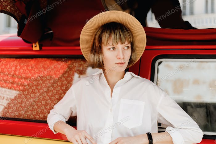 Stylish young woman in a straw hat dressed in white shirt stands next to the a bright red and yellow