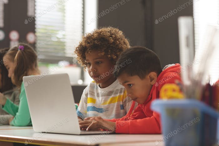 Front view of two school kids working on one laptop in classroom against school girl in background