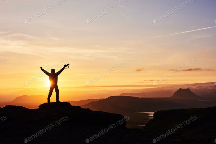 Silhouette of a man on a mountain top. Person silhouette on the rock. Sport and active life concept