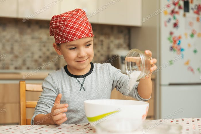 Boy is cooking in a luminous kitchen adding ingredients