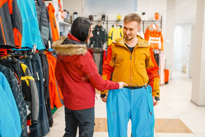 Couple buying skiing or snowboarding equipment