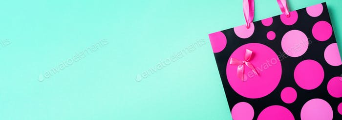 Top view of pink paper shopping bag on trendy green background. Copy space. Gift concept. Woman&#39