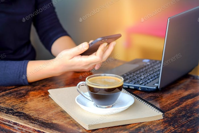 Business people working smart phone with coffee on notebook.