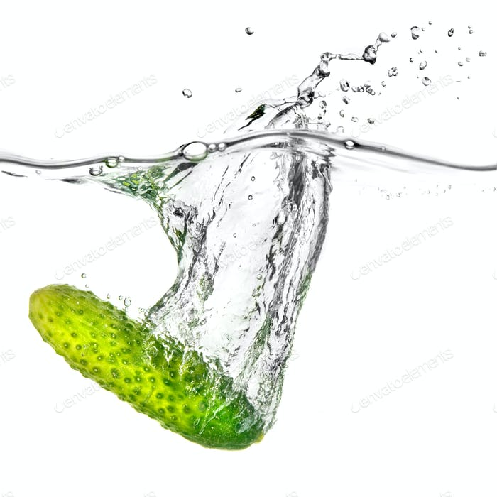 green cucumber dropped into water isolated on white