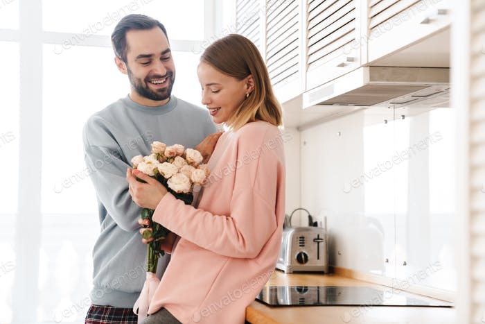 Portrait of cheerful man giving his smiling girlfriend flower bouquet