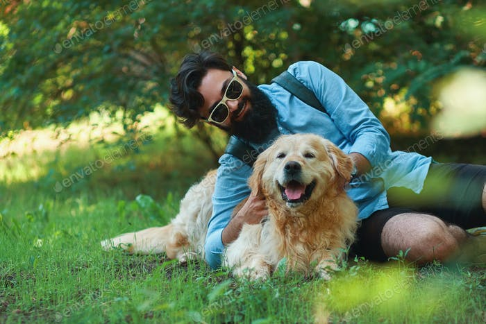 Man with beard and his small yellow dog playing and enjoying sun