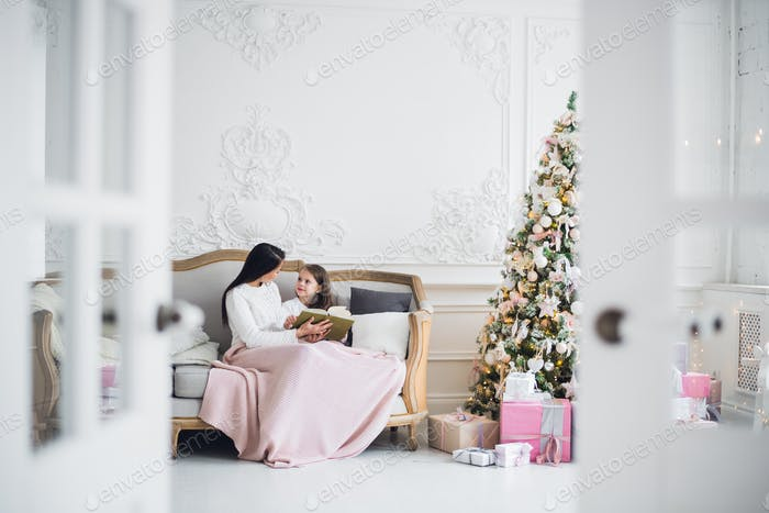 Frohe Weihnachten und frohe Feiertage. ziemlich junge Mama Lesen ein Buch zu Ihr Niedlich Tochter in der Nähe