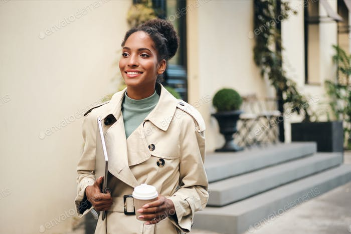 African American business woman in stylish trench coat confidently walking down the street