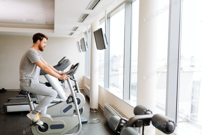 Sportive male exercising on bicycle