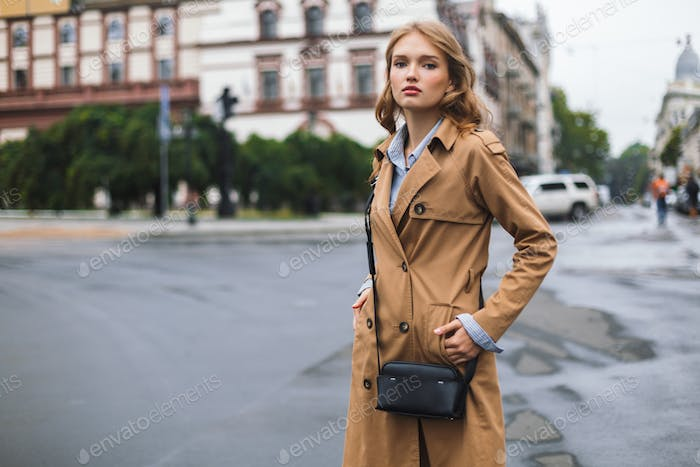Young attractive woman in trench coat with little black cross ba