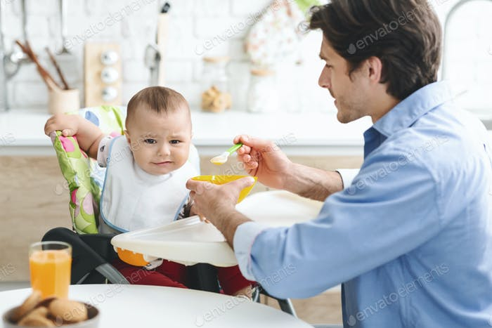 Dad feeding his baby with healthy untasty food