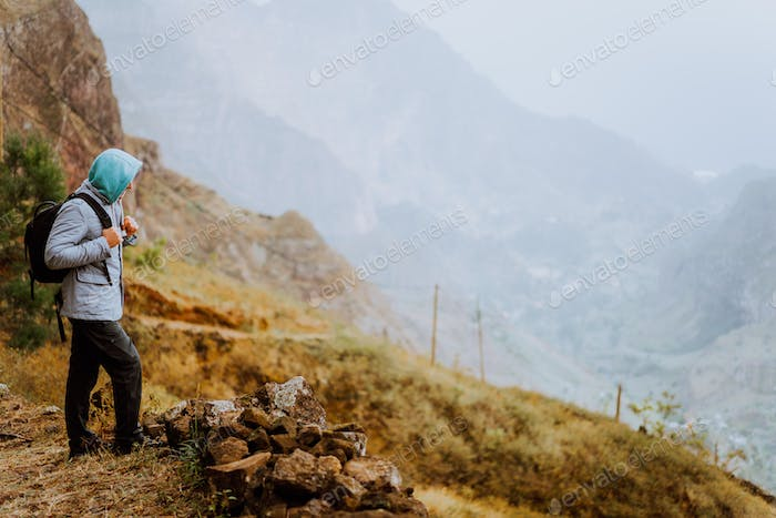 Male hiker looking down to Xo-Xo Valley. Santo Antao Island, Cape Verde. Traveler on mountains cliff