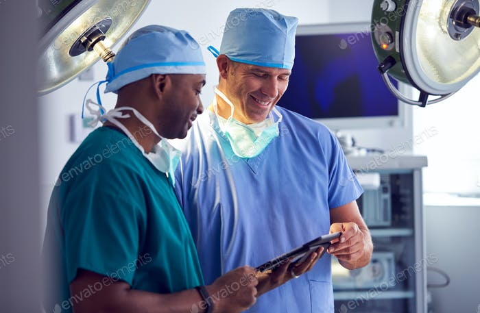 Male Surgeons Wearing Scrubs Looking At Digital Tablet In Hospital Operating Theater