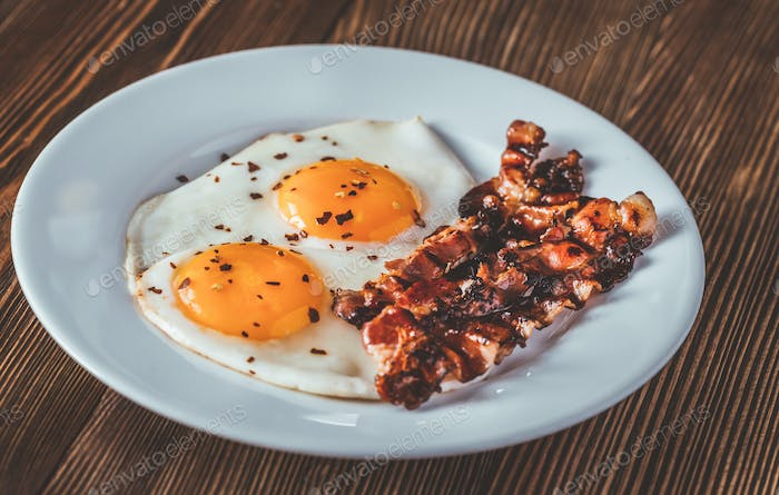 Fried eggs and bacon on the white plate